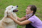 Child embracing dog on a meadow — Stock Photo