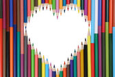 Colored pencils forming a heart love topic — Stok fotoğraf