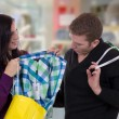 Couple with shopping bags buying clothes in a clothing store — Stock Photo #38294999