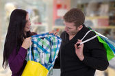 Couple with shopping bags buying clothes in a clothing store — Stock Photo