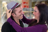 Couple trying on a hat while shopping in a clothing store — Photo
