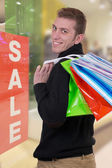 Smiling man with shopping bags in a clothing store — Stock Photo