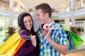 Young couple having fun while shopping in a shopping mall — Stockfoto