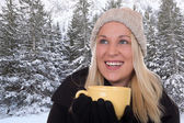 Young blond woman drinking outdoors in winter cup of tea — Stock Photo