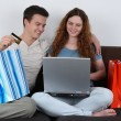 Young couple with shopping bags doing internet shopping — Stock Photo #41606609