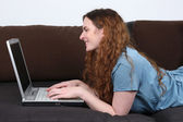 Young woman lying on sofa and using her laptop computer — Stock Photo