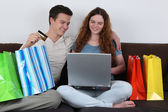 Young couple with shopping bags doing internet shopping — Stock Photo
