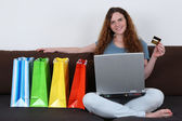 Young woman with laptop computer doing internet shopping — Stock Photo
