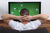 Young man watching football on tv — Stock Photo