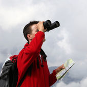 Searching the destination with binoculars in the mountains — Stock Photo