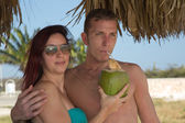 Young people on vacation drinking from coconut — Stock Photo