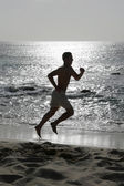 Young man running or jogging on the beach — Foto de Stock
