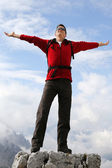 Happy young mountaineer on top of mountain success topic — Stock Photo