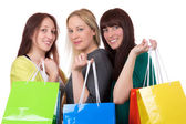 Group of smiling young women having fun while shopping — Stock Photo
