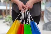 Woman holding colored shopping bags in a mall in her hand — Stock Photo