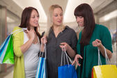 Group of young women talking about their purchase in shopping ma — Stock Photo