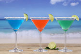 Martini Cocktails in glasses on the beach with lemons — Stock Photo
