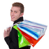 Smiling young man with shopping bags — Stock Photo