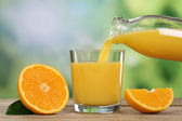 Orange juice pouring into a glass in summer — Stock Photo