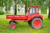 Retro red agricultural tractor under birch trees — Foto Stock