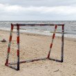 Steel metal football goal gate on sea sand — Stok fotoğraf