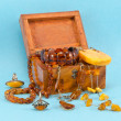 Amber apparel jewelry retro wooden box on blue — Foto de stock #12640157
