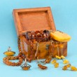 Foto Stock: Amber apparel jewelry retro wooden box on blue