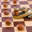 Foto Stock: Gold crocodile nut crush tool on chess board