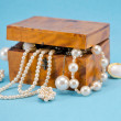 Pearl jewelry defocus in retro wooden box on blue — Foto Stock
