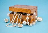 Pearl jewelry defocus in retro wooden box on blue — Stock Photo