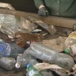 Recycling. pet bottles ride escalator and man hands sorts them. — Stock Video