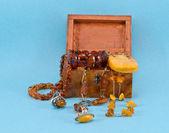 Amber apparel jewelry retro wooden box on blue — Stock Photo