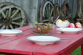 Salad glass dish and apples wooden homestead table — Stock Photo