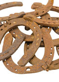 Stack of old retro horse shoes isolated on white — Stock Photo
