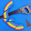 Concept rainbow cut with hand saw blue background — ストック写真