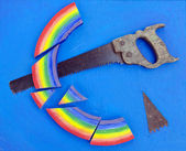 Concept rainbow cut with hand saw blue background — 图库照片