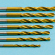 Various size golden drill bits on blue — Stock Photo
