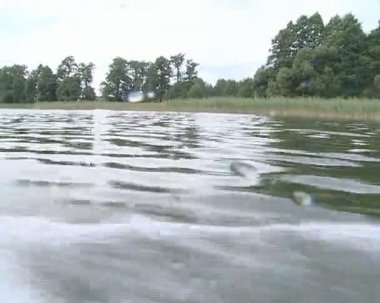 Lake water splashing on camera lens filmed aboard the motor boat — Stock Video
