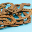 Stack of old retro horse shoes on blue — Stock Photo