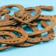 Stack of old retro horse shoes on blue - Stock Photo