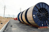 High voltage cable reels and road construction — Stock Photo