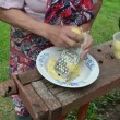 Stock Video: Old woman grater potato