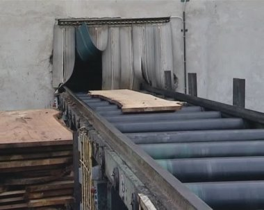 Boards moving on escalator from outside to sawmill. — Stock Video