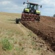 Stock Video: Heavy tractor plow field