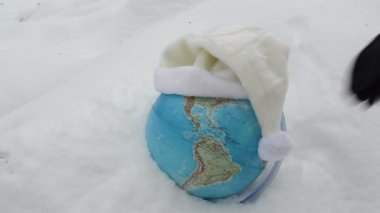 Earth globe sphere in winter snow snowbank and hand take off white cap concept.