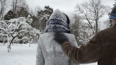 Man hand clean snow from woman coat in winter.