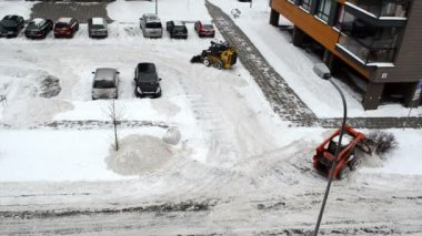 VILNIUS, LITHUANIA - CIRCA DECEMBER 2012 - cars stand in flat block house parking and tractors excavators work clean winter snow circa December 2012 in Vilnius.