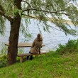 Royalty-Free Stock Photo: Woman sit wooden bench willow tree admire lake