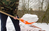 Man camouflage shovel tool clean snow roof winter — Stock Photo