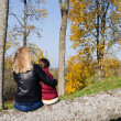 Mother sit broken tree daughter admire autumn - Stock Photo